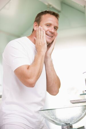 nightclothes: Man in bathroom applying aftershave and smiling Stock Photo