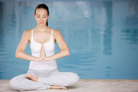 Woman sitting poolside doing yoga Stock Photo - 3477469