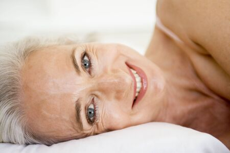 sexy middle aged woman: Woman lying in bed smiling
