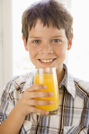 Young boy indoors drinking orange juice smiling Stock Photo - 3507095