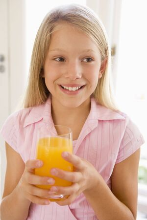 Young girl indoors drinking orange juice smiling photo