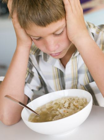 fussy: Young boy in kitchen eating soup Stock Photo