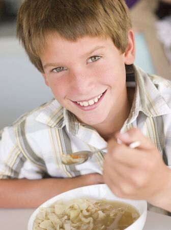Young boy in kitchen eating soup and smiling photo