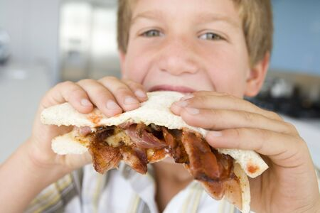 bacon portrait: Young boy in kitchen eating bacon sandwich Stock Photo