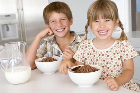cereal bowl: Two young children in kitchen eating cereal smiling