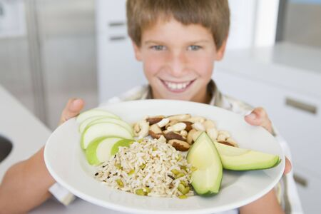 Young boy in kitchen eating rice fruit and nuts smiling Stock Photo - 3506679