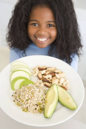 Young girl eating cereal in living room smiling Stock Photo - 3477390
