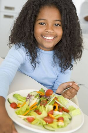childrens food: Young girl in kitchen eating salad smiling Stock Photo
