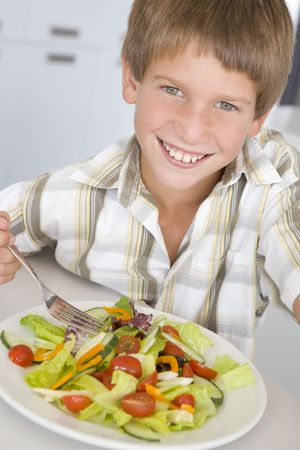 childrens food: Young boy in kitchen eating salad smiling