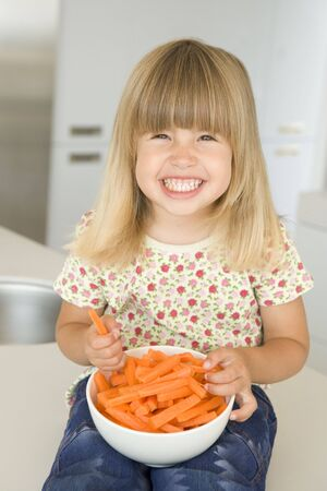 snacking: Young girl in kitchen eating carrot sticks smiling