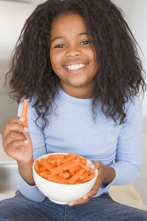ni�os comiendo: Ni�a comiendo plato de verduras en sala sonriendo