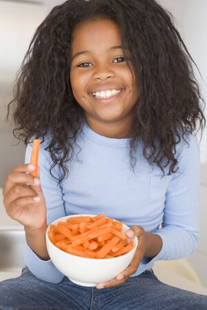 children eating: Young girl eating bowl of vegetables in living room smiling Stock Photo