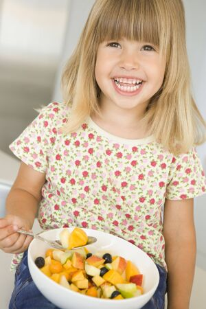 Young girl in kitchen eating bowl of fruit smiling photo