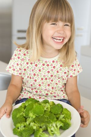 green's: Young girl in kitchen eating broccoli smiling