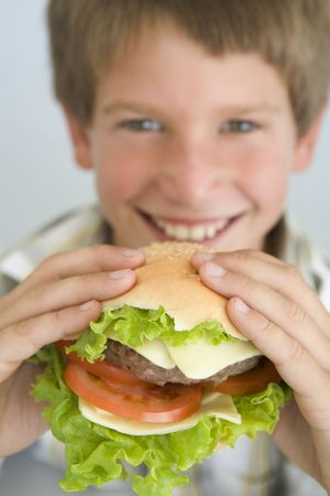 Young boy eating cheeseburger smiling photo