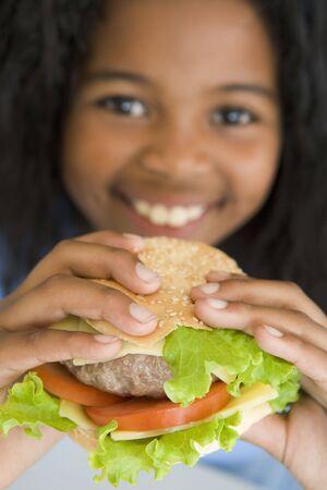 Young girl eating cheeseburger smiling photo