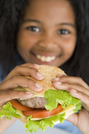 childrens food: Young girl eating cheeseburger smiling