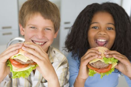 messy eater: Two young children in kitchen eating cheeseburgers smiling Stock Photo