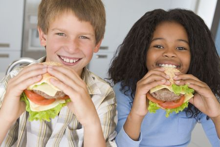 childrens food: Two young children in kitchen eating cheeseburgers smiling Stock Photo