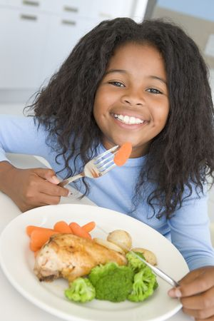 childrens meal: Young girl in kitchen eating chicken and vegetables smiling Stock Photo