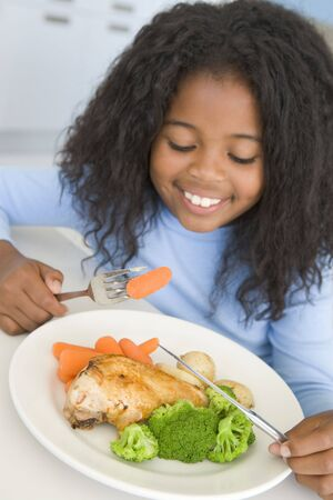 Young girl in kitchen eating chicken and vegetables smiling Stock Photo - 3506976