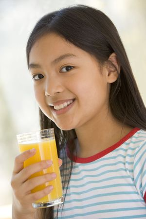 childrens food: Young girl indoors drinking orange juice smiling Stock Photo