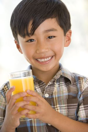 Young boy indoors drinking orange juice smiling photo