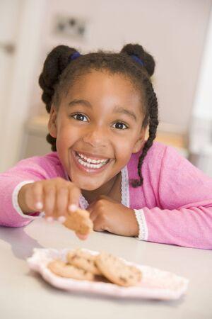 galleta de chocolate: Ni�a en la cocina comiendo galletas sonriente