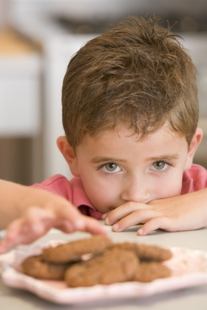 Young boy in kitchen eating cookies photo