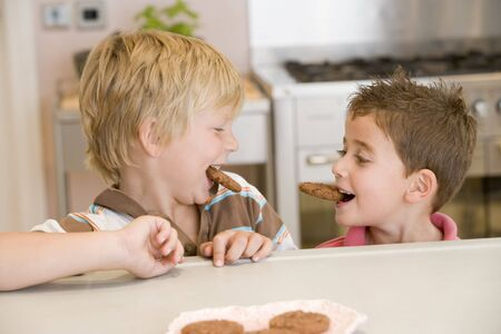 childrens food: Two young boys in kitchen eating cookies smiling