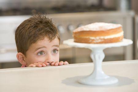 snoepjes: Jongen in de keuken te kijken naar taart op counter Stockfoto