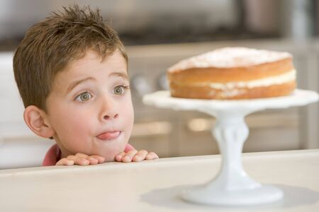 Young boy in kitchen looking at cake on counter photo