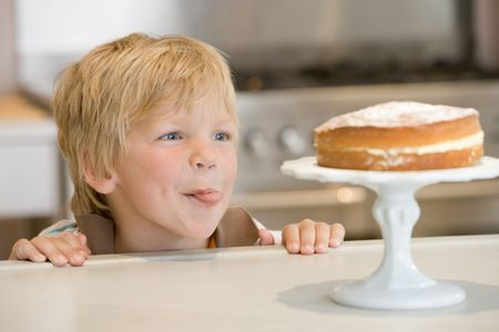 tempted: Young boy in kitchen looking at cake on counter