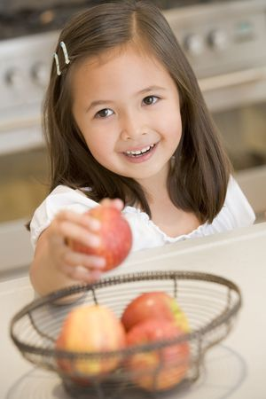 snacking: Young girl in kitchen getting apple off counter smiling Stock Photo