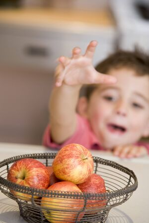 snacking: Young boy in kitchen getting apple off counter