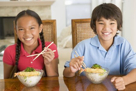 eating utensils: Two young children eating Chinese food in dining room smiling