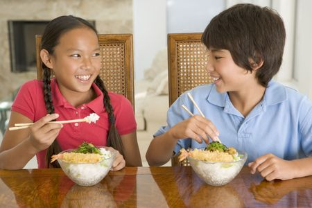 childrens food: Two young children eating Chinese food in dining room smiling