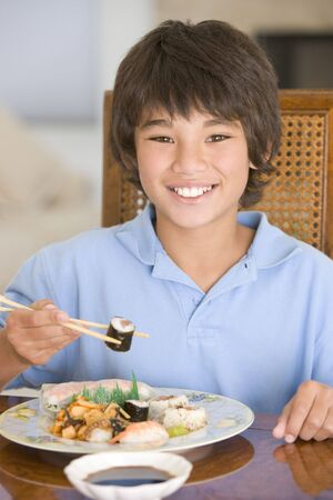 Young boy in dining room eating chinese food smiling Stock Photo - 3507010