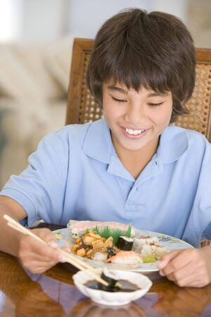childrens food: Young boy in dining room eating chinese food smiling