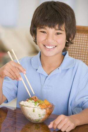 eating out: Young boy in dining room eating chinese food smiling