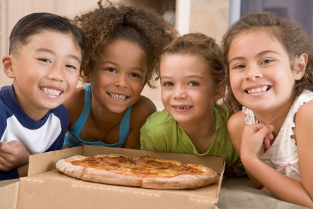 pepperoni pizza: Four young children indoors with pizza smiling Stock Photo