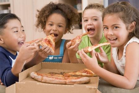 Vier jonge kinderen binnenshuis eten pizza glimlachende