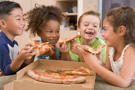 indoors: Four young children indoors eating pizza smiling