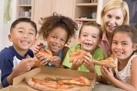 Four young children indoors with woman eating pizza smiling photo