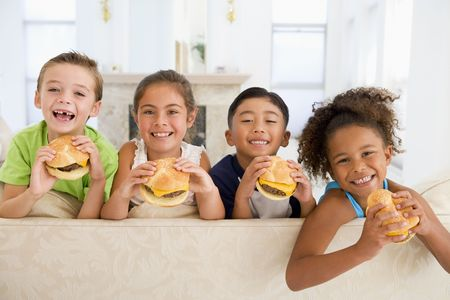 eating out: Four young children eating cheeseburgers in living room smiling