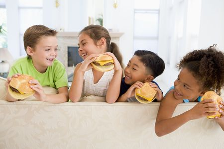 childrens food: Four young children eating cheeseburgers in living room smiling