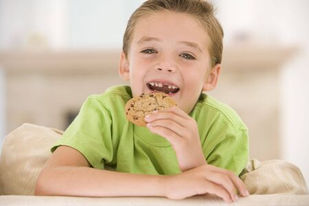 eating in: Young boy eating cookie in living room smiling