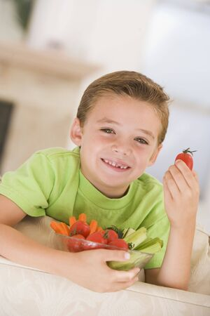 offset angle: Young boy eating bowl of vegetables in living room smiling