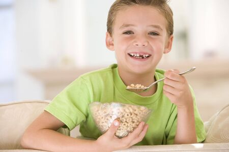 Young boy eating cereal in living room smiling photo