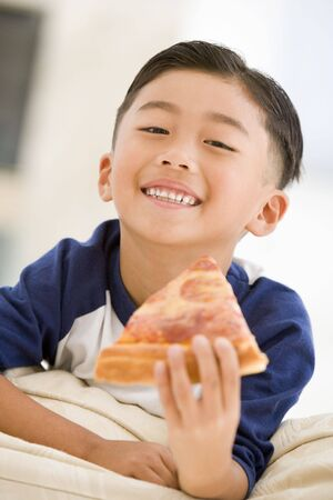 eating out: Young boy eating pizza slice in living room smiling Stock Photo